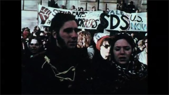 1960s: Woman speaks into microphone. People march and chant. Police escort people away.