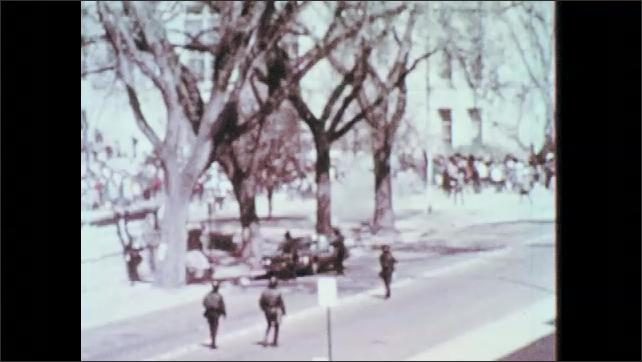 1960s: Man lights fire on street. People run through street and grass. Policeman help officer take helmet off, officer stumbles.