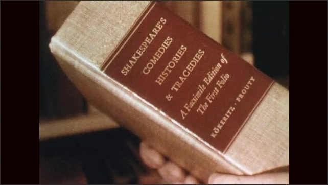 1950s: Hand selects book off shelf. Spines of books on shelf