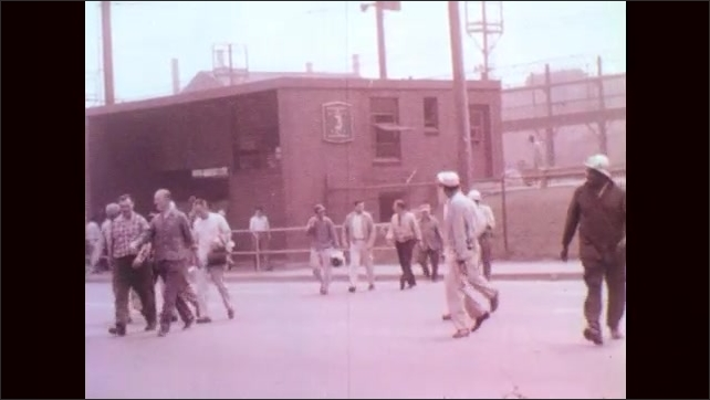 1950s: Crowd of workers, some in helmets, exit building by fence and train line.
