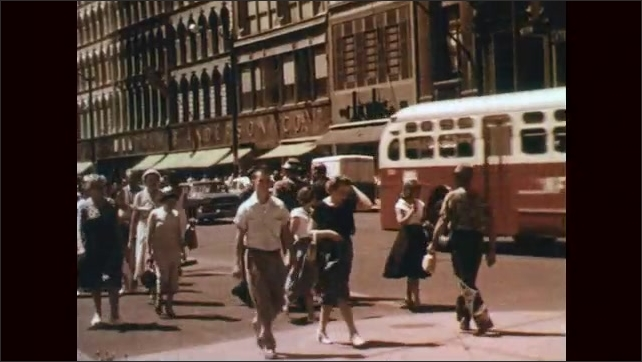 1950s: Hands hold and open financial mathematics book, hand turns pages. People cross city street past buildings, cars and truck.