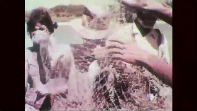 1960s: Pelican lands in ocean water. Pelicans float on ocean waves. Men stand in ocean and drag net. Fish flop in net. Men and women work on boat. Men sail boat to shore. Hands wrap fish in leaf.
