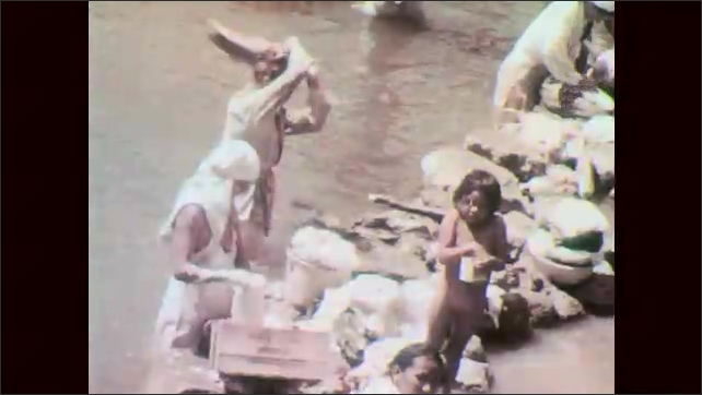 1960s: People walk through market. People sit at stalls in market. Women wash clothes at river's edge. Water fountain in city center. Men use machines to pound ground in city.