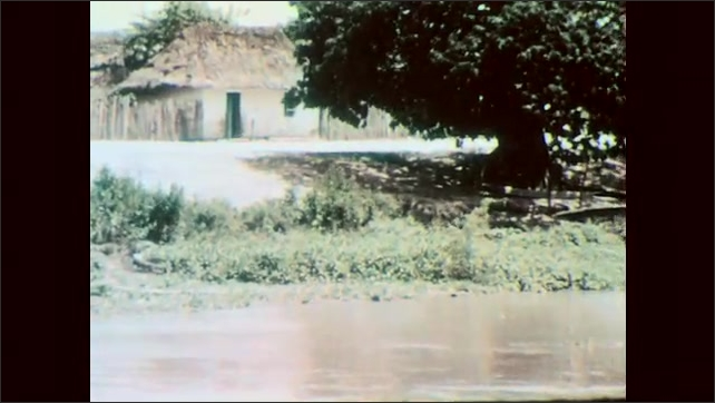 1960s: Homes and trees on edge of river. People and homes on edge of river. Men pan for gold in river. Man swirls gold pan around in water. Water spins in pan.