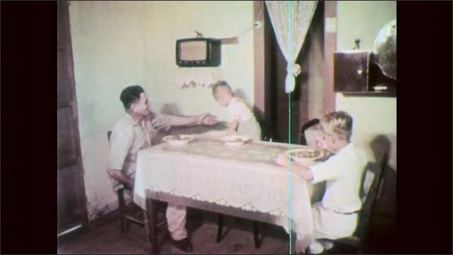 1960s: Man lifts child onto highchair. Woman serves food to family at dinner table. Boy eats from bowl. Man and child eat from bowls. Large city vista.