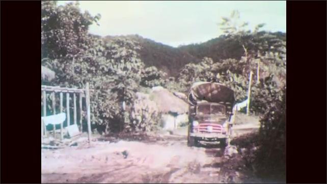 1960s: Stream in arid landscape. Truck struggles along muddy rough road. Men ride mules through flooded area. Jeep drives through flooded road.