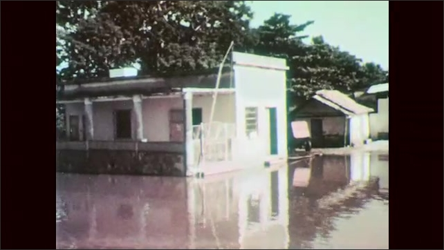 1960s: Girl pulls herself across river on makeshift cable car. Man rows bow down flooded street. Flooded buildings.