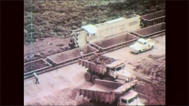 1960s: Crane dumps ore into dump truck. Dump truck drives along dirt road. Trucks empty contents into train cars. Train pulls cars of ore through countryside. Ore travels up conveyor to storage.