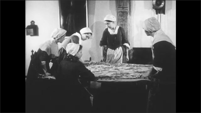 1700s Recreation: Women in bonnets pull on string, string it taught across tablecloth, pluck string. Women sit at table working over tablecloth strings. Girl sits by fire working on hand loom.