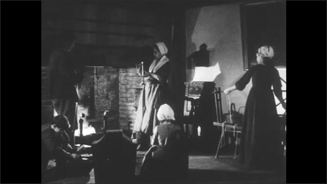 1700s Recreation: Woman places candle into holder. Daughters, father, mother, and son father around fireplace, mother lights candle. Woman walks out of room, man sits down with stick.