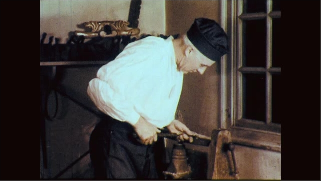 1960s: man turns large wheel with belt attached, man carves spinning piece of wood
