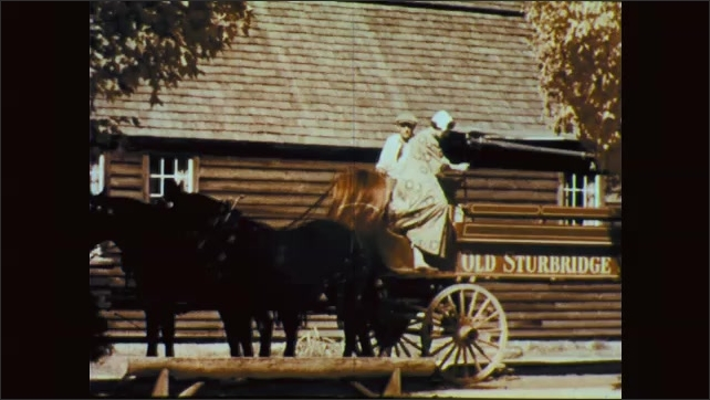 1960s: 2 horses pull carriage with man and woman seated, carriage stops in front of cabin, woman carefully steps down from carriage, waves, carriage pulls away