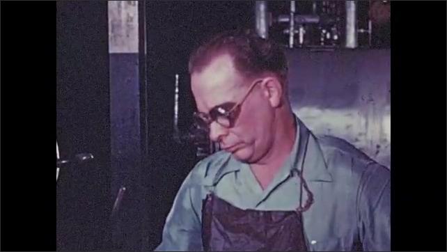 1950s: Man spins wheel. Man guides metal rods through machine. Man looks at parts through magnifying glass, writes on paper.