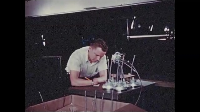 1950s: Man removes parts from vehicle wheel assembly. Man stands at table, writes on tags.