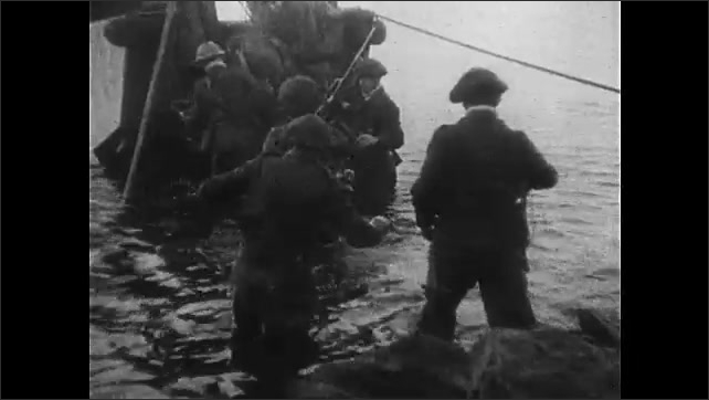 1940s: Dead soldier lies in snow. Soldiers walk on snowy shore of island. Soldiers line up and board personnel boats. PT boats pull from shore. Soldier fires machine gun from boat.