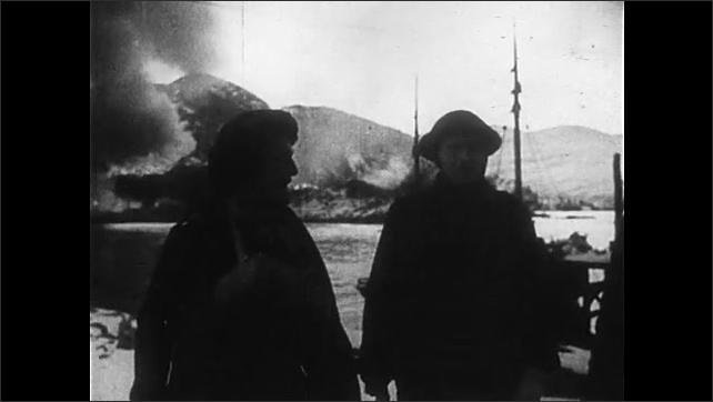 1940s: Soldiers stand.  Men run.  Explosions.  Fire.  Men march.