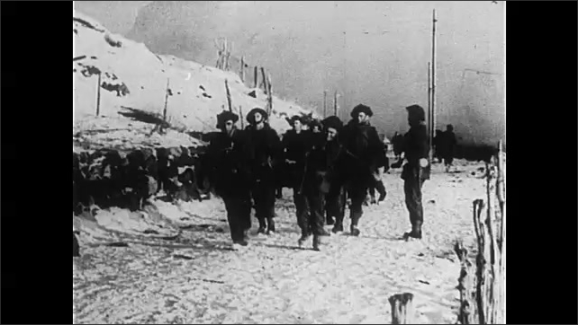 1940s: Airplane.  Smoke-filled sky.  Village.  Men on boat.  Soldiers move machine gun.  Men march through snow.  Medics carry patient on stretcher.