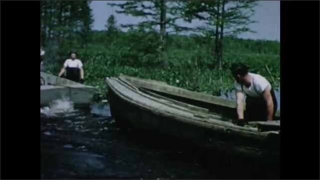 1950s: Crew of fishermen on boats pull river net from shore to shore using a setting boat. Net creates circular area in river. Men prepare setting boat.