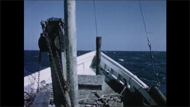 1950s: Man stands at bow of boat. Boat bobs up and down. Men stand at bow of boat, pull up rope.
