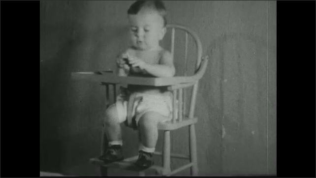 UNITED STATES 1930s - Baby in highchair with a biscuit.