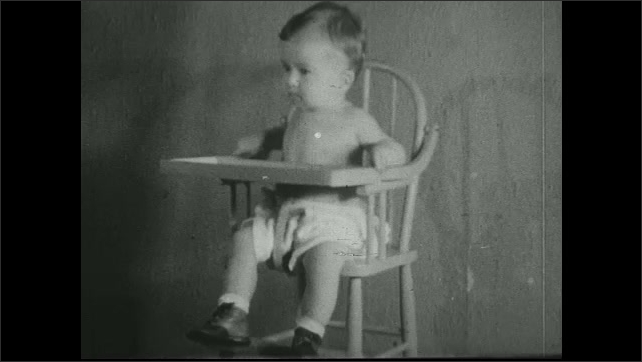 UNITED STATES 1930s ?????Woman seats baby in highchair and gives it a spoon.