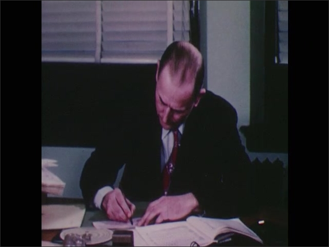 1950s: Man sits at desk in office holding paper. He looks at paper and signs end of it. Woman approaches man at desk, man hands woman paper. Woman seals paper in envelope.