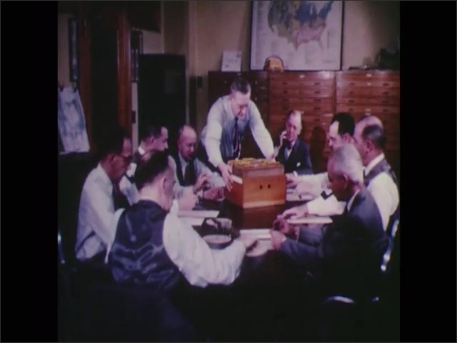 1950s: Man in uniform unlocks door in building for men in suits to walk through. Guard closes and locks door after men go through. Men sit around desk looking through files.