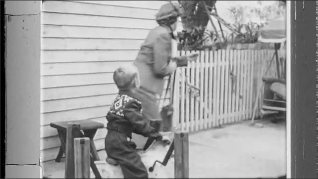 1950s: Woman and boy walk out of house, woman sets boy on toy horse. Woman exits backyard, closes gate behind her, says goodbye to boy.