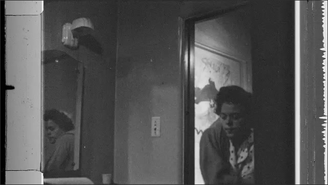 1950s: Woman stumbles out of bed, stumbles into bathroom, opens medicine cabinet, knocks bottles from cabinet.