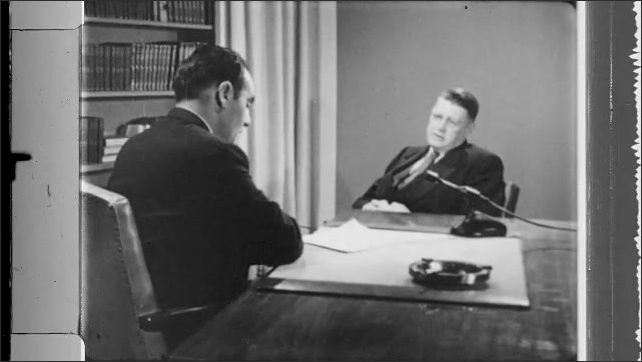 1950s: Man sits at desk, asks man questions, writes on paper.  Man sits by desk, talks.