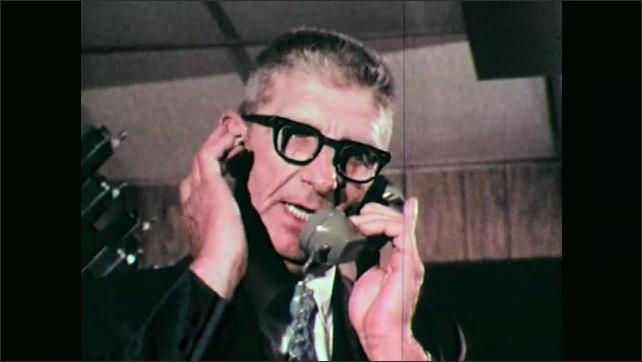 1970s: UNITED STATES: man speaks on telephone. Man scratches face. Civil Defense badge on uniform.