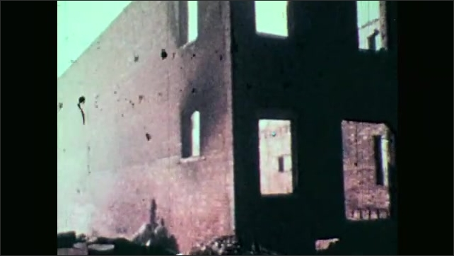 1970s: View of burned buildings and debris.