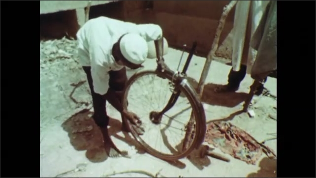 1960s: AFRICA: metal pots for sale in market. Man repairs metal pots. Man repairs bicycle wheel. Carpenter in Africa. Scientific and commercial agriculture in Africa. Men walk in field of crops.