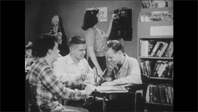1950s: Three boys sit at table in drug store talking while girl stands talking on payphone behind them. Girl hangs up phone and sits at table with other girls.