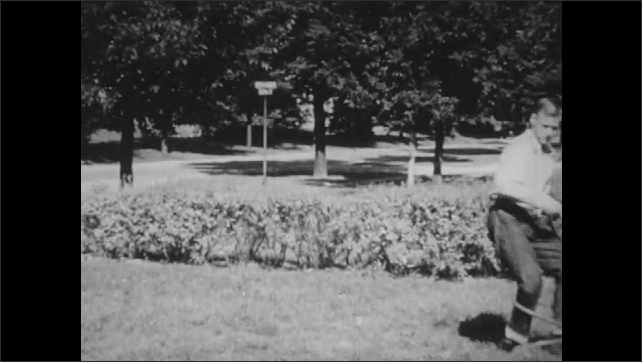 1950s: Boy runs across lawn carrying books. He jumps over hedge and slips on wet grass. He stands up, gets angry and picks up sprinkler from lawn and tosses it. He stands looking down and walks off.