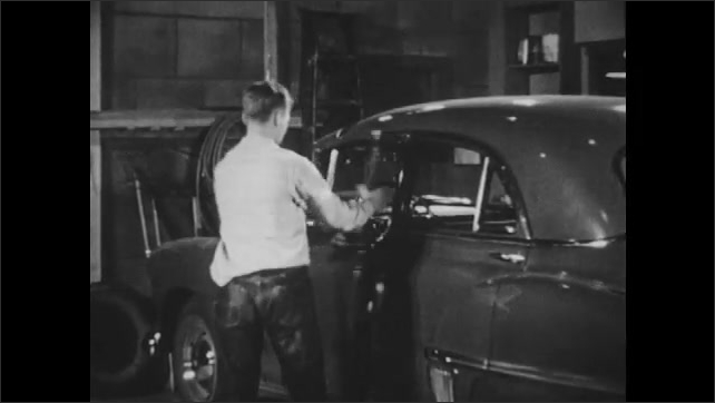 1950s: Boy approaches garage, opens doors, and goes inside. He gets inside car in garage and hits engine button. He hits engine button repeatedly.