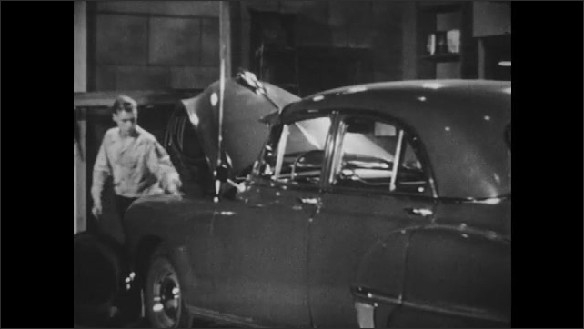 1950s: Boy sits behind wheel of car in garage, angrily hitting ignition button. He gets out, opens hood of car, and hits head on hood. He grabs tool and goes to engine.