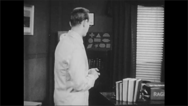 1950s: Man stands in front of desk in office pointing at block on desk with words on them: Rage, Fear, Love. Man talks while talking behind desk.