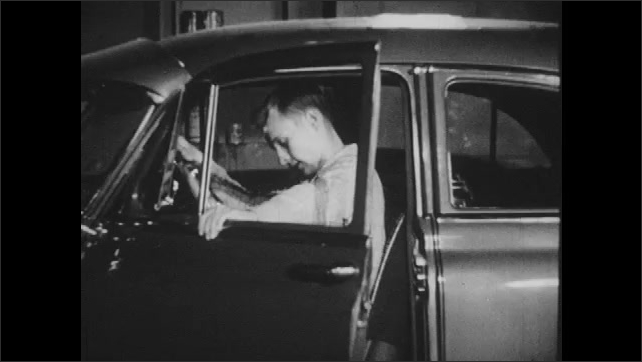 1950s: Boy sits in car that won't start, in garage. Boy gets out of car and leaves garage.