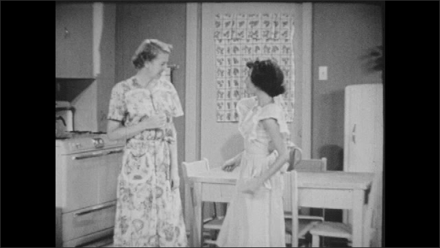 1950s: Boy leaves garage, looks back at car, shrugs and walks away. Mother and daughter are talking in kitchen when boy enters. Boy watches them hug, smiles then leaves room.