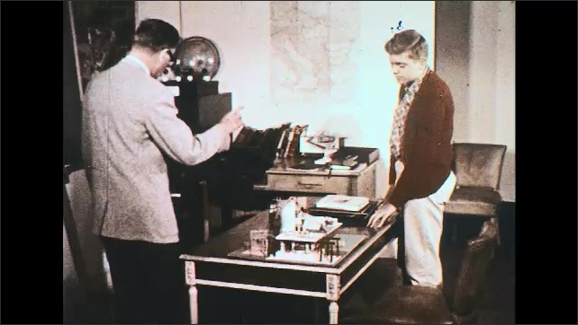 UNITED STATES 1950s: Man and boy at desk, look at power plant model, man takes picture from drawer.