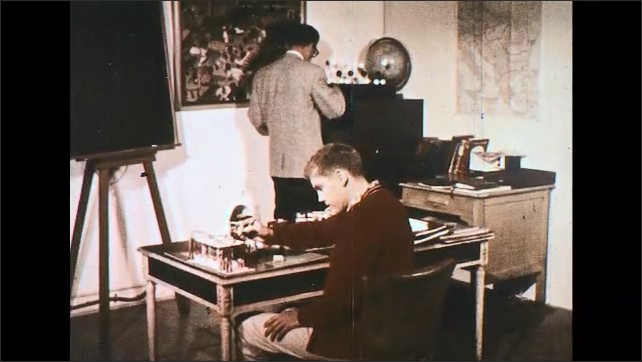 UNITED STATES 1950s: Dissolve, boy sits at desk, works on model, man approaches desk.