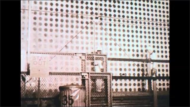 UNITED STATES 1950s: Tilt down uranium graphite pile reactor, worker lowers on platform.