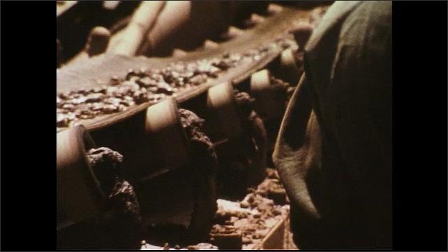 UNITED STATES 1970s : Man Shovelling Ore Onto a Moving Conveyor Belt Inside Mine