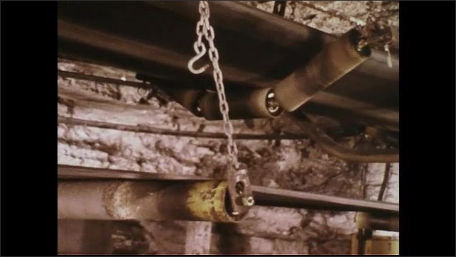 UNITED STATES 1970s : Man Assesses Integrity of Conveyor Belt Parts Inside Mine