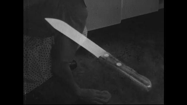 Woman slides knife back and forth on sharpener to make it sharper.