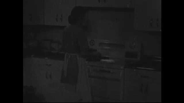 A woman cleans a stovetop and cooks on it.