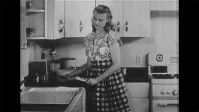 1950s: Woman opens oven, pulls out pans with flat cake, looks disappointed. Woman sits down at table, flips through cookbook.