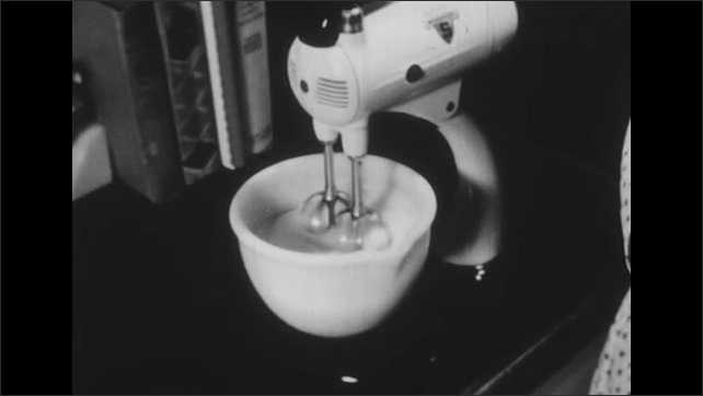 1950s: Woman stirs ingredients together in a bowl. Electric Beater beats egg whites stiff. Woman pour batter from one bowl to another.