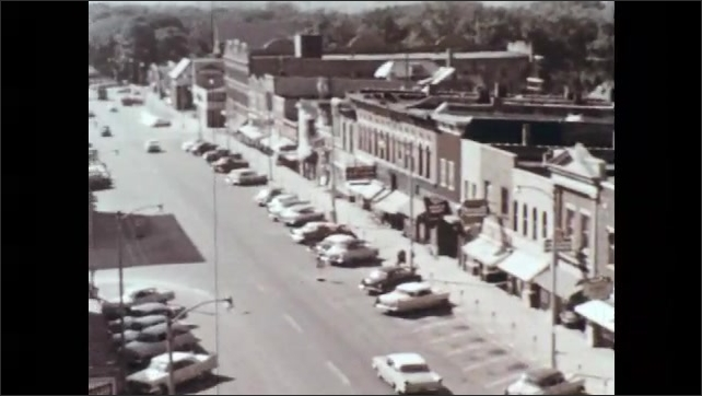 1960s: UNITED STATES: buildings in town. Overhead view of car driving along road. County Court House building in settlement. Stores along main street. Trading centre of town. Signs on buildings.